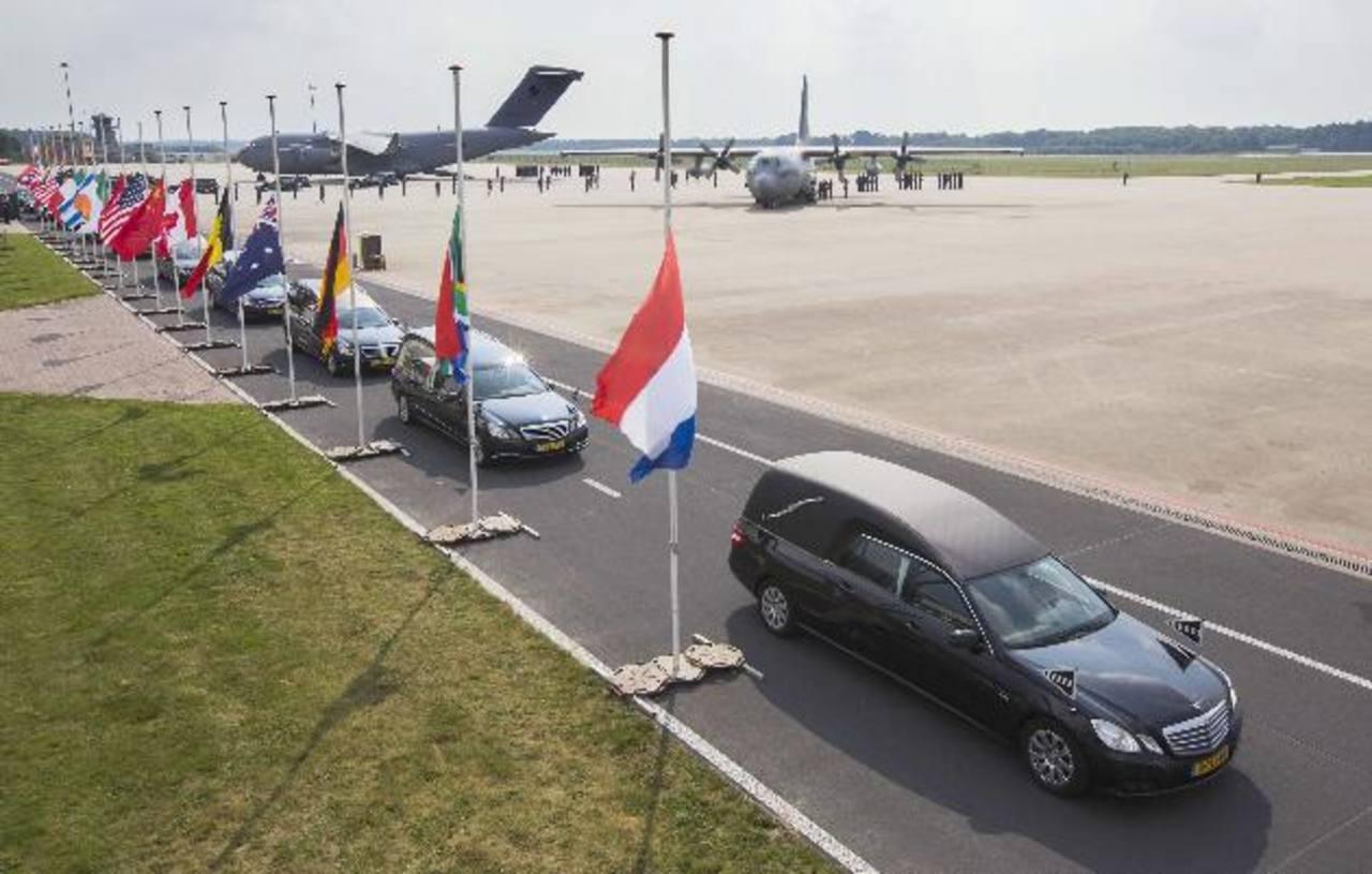 Coches fúnebres llevan ataúdes con los restos de las víctimas del avión MH17 en aeropuerto militar en Holanda. foto edh /EFE