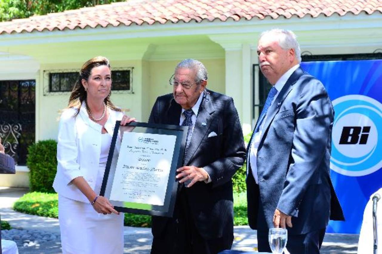 María Alicia Mayorga de Pérez y Juan Miguel Torrebiarte, ambos del Banco Industrial, entregaron un diploma de reconocimiento al Dr. Alfredo Martínez Moreno. foto edh / Omar Carbonero