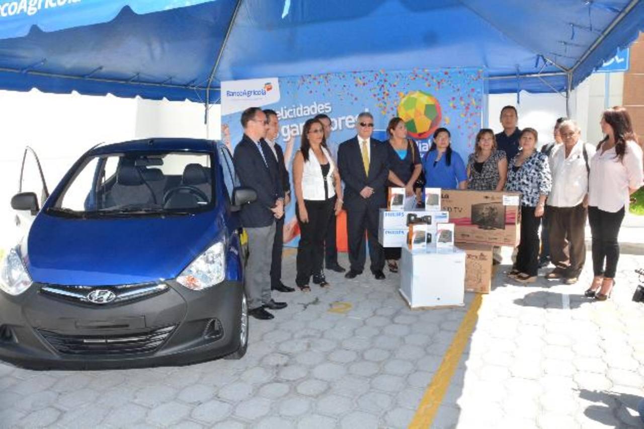 Representantes del Banco Agrícola otorgan el premio principal, un Hyundai del año, y otros premios a los felices ganadores de la promoción. Foto EDH / David Rezzio