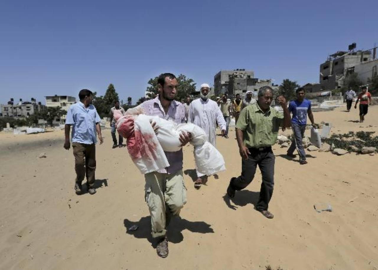 Un palestino carga el cuerpo de su hijo de cuatro años, quien murió durante los bombardeos en Gaza. foto edh / AP