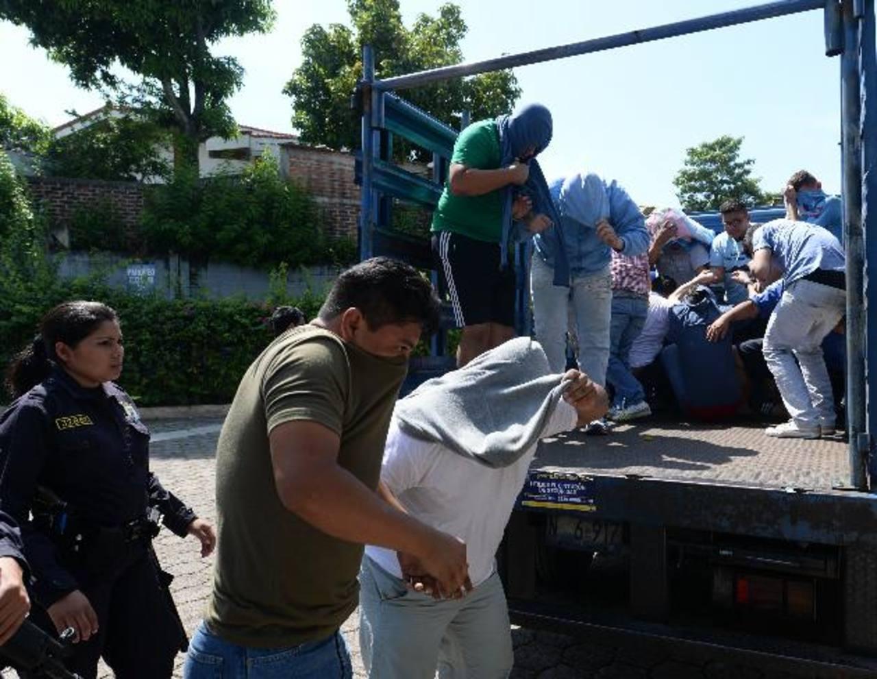 Policías custodian a las 37 personas acusadas de haber participado en los desórdenes causados el domingo anterior, tras el partido entre los equipos Alianza y Águila. Foto EDH /Marlon H.