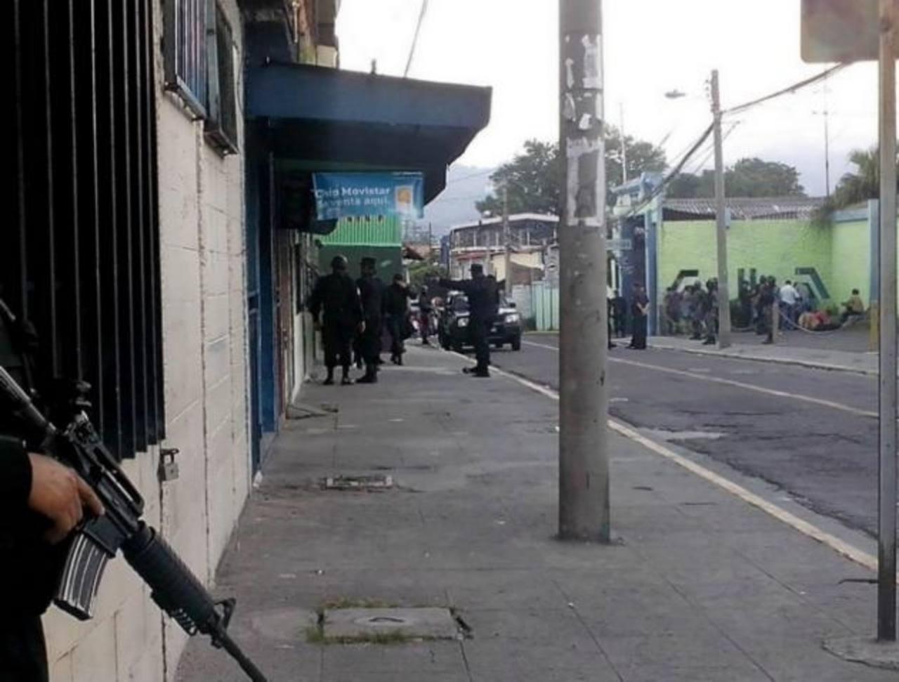 Uno de los sospechosos es sacado del establecimiento por los agentes policiales.