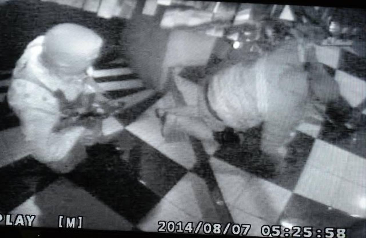 Un ladrón somete a un vigilante encañonándolo con un fusil en las gradas de la entrada principal del negocio. Al mismo tiempo, el otro guardia es sometido. Foto EDH / Cortesía