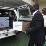 El viceministro de Sanidad para Servicios de Prevención liberiano, Tolbert Nyenswah, lleva una caja del tratamiento experimental contra el ébola Zmapp.