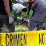 Forenses examinan uno de los cadáveres que quedaron tendidos ayer frente a la morgue en San Pedro Sula. foto edh/EFE