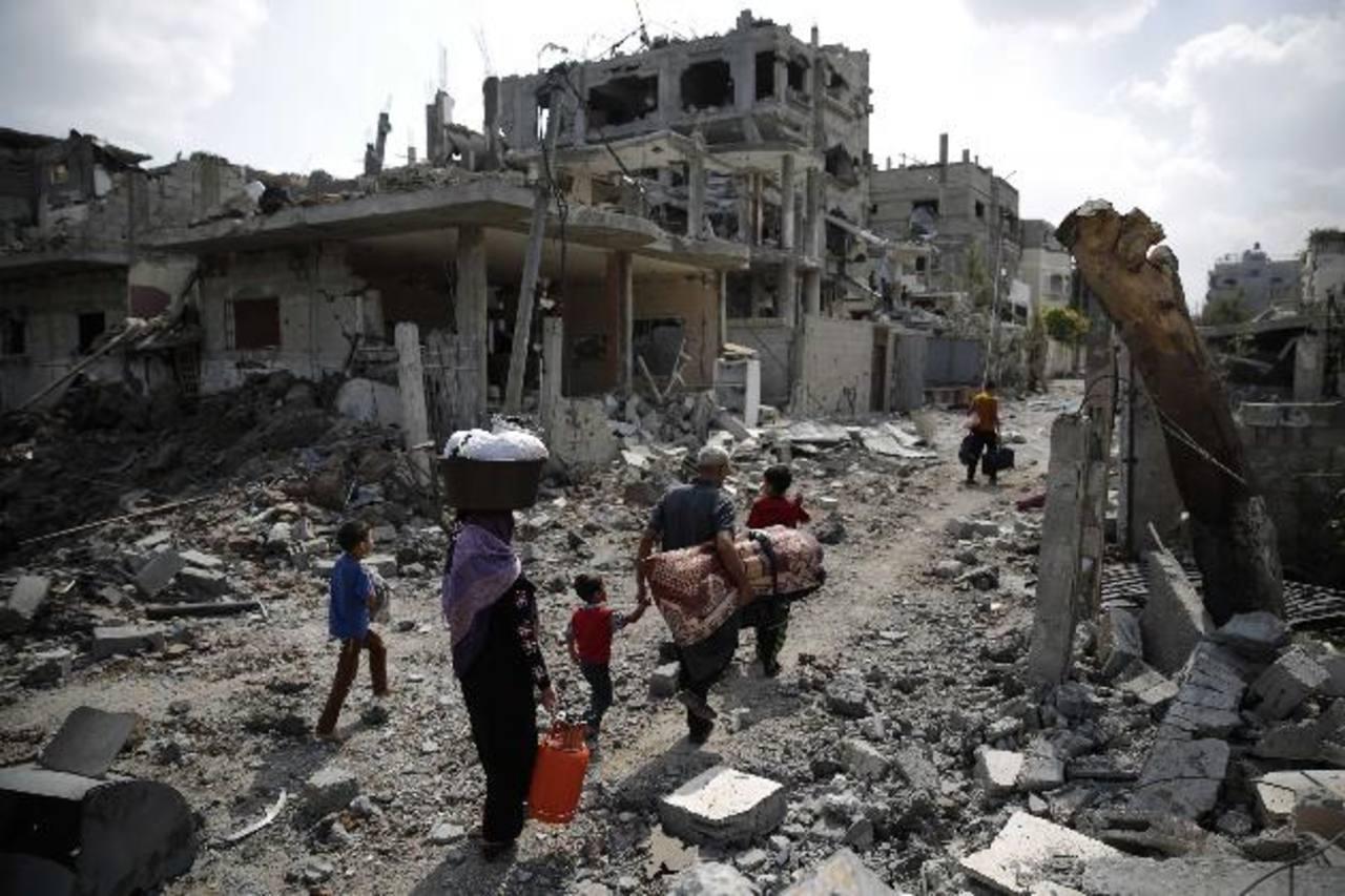 Una familia palestina regresa con sus pertenencias a los restos de su casa. foto edh / reuters