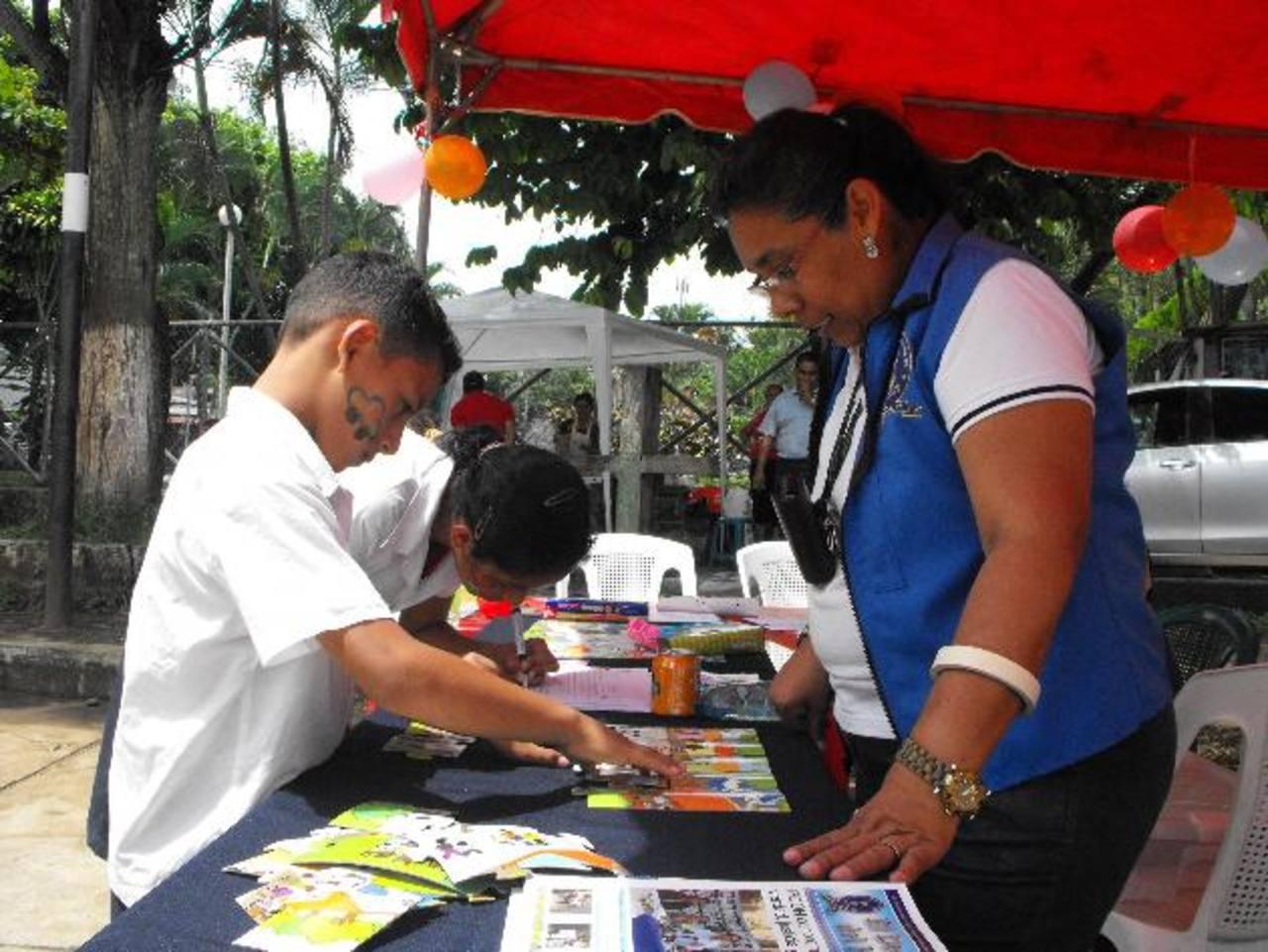 Niños reciben materiales educativos en la feria.