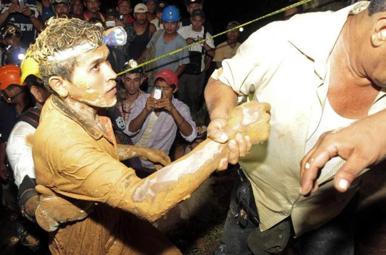 Uno de los 20 mineros es auxiliado por socorristas, que los rescataron la noche del viernes. Foto EDH / Reuters. Rescatistas en la mina de oro del cerro El Comal, en Bonanza, caribe Norte, donde ayer continuaban la búsqueda de mineros.