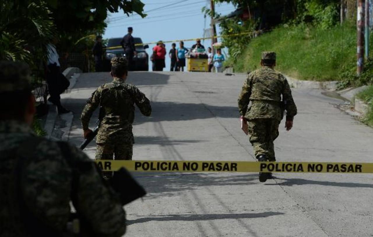 Soldados resguardan el sitio de un asesinato. Las cifras de la PNC registran 889 homicidios más que en 2013. Foto EDH / m. Hernández