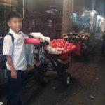 Este niño no pierde su sonrisa al ofrecer sus tomates, aún con su mochila a su espalda.