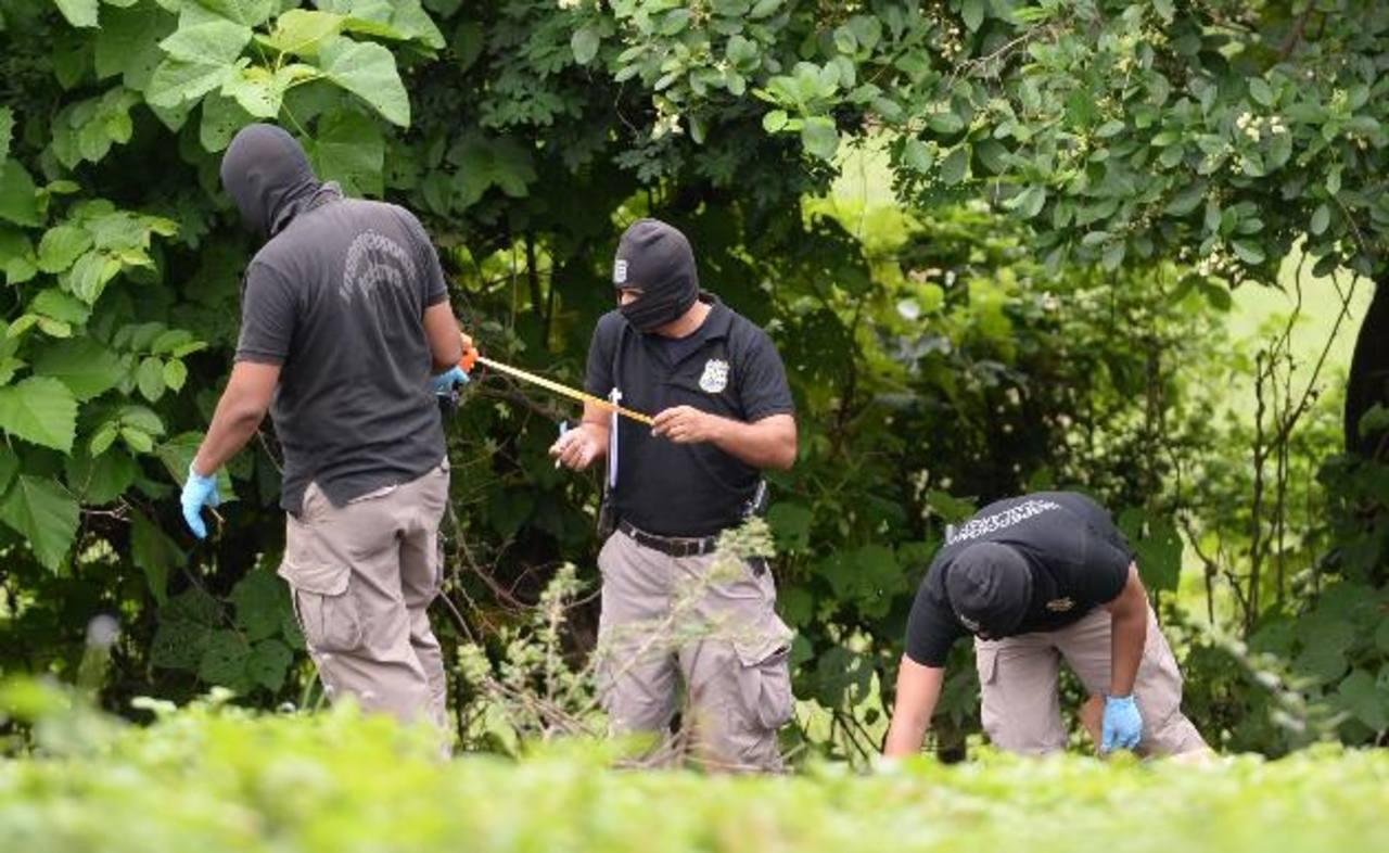 Investigadores recolectan evidencias en el sitio donde asesinaron a dos hombres en San José Villanueva. Foto EDH / Archivo