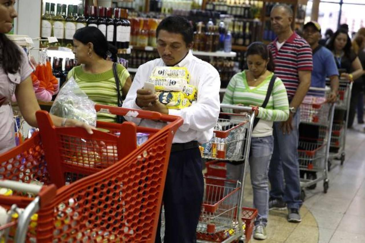 Un grupo de venezolanos hace fila para pagar sus compras en un supermercado de Caracas, Venezuela. foto edh /Reuters.
