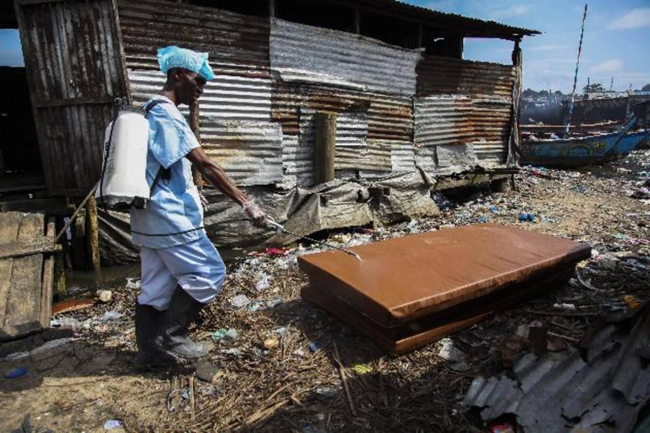 Un enfermero liberiano desinfecta unos colchones que fueron sacados de un centro de aislamiento en Liberia.