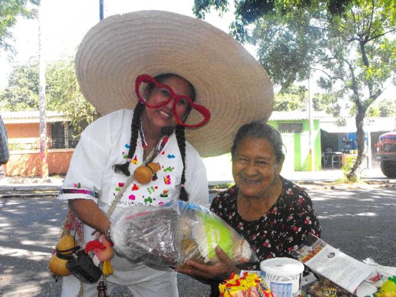 La Cipitía santaneca entregando donativo de víveres a una de las beneficiadas, Dora Rodríguez. En ocasiones, también le ha donado producto para surtir su venta. fotoS edh / Mauricio Guevara