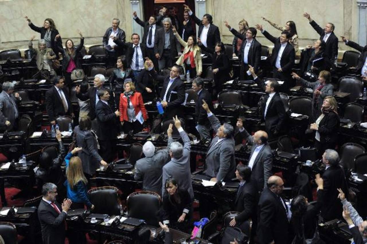 Diputados oficialistas celebran este jueves la aprobación de una ley que permite el pago en Argentina de la deuda reestructurada.