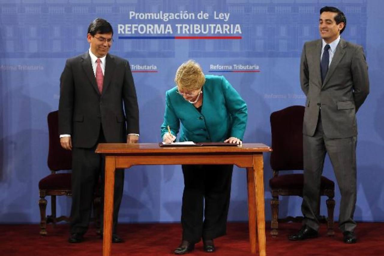La presidenta de Chile, Michelle Bachelet (c), firmó ayer la ley de reforma tributaria. foto edh/EFE