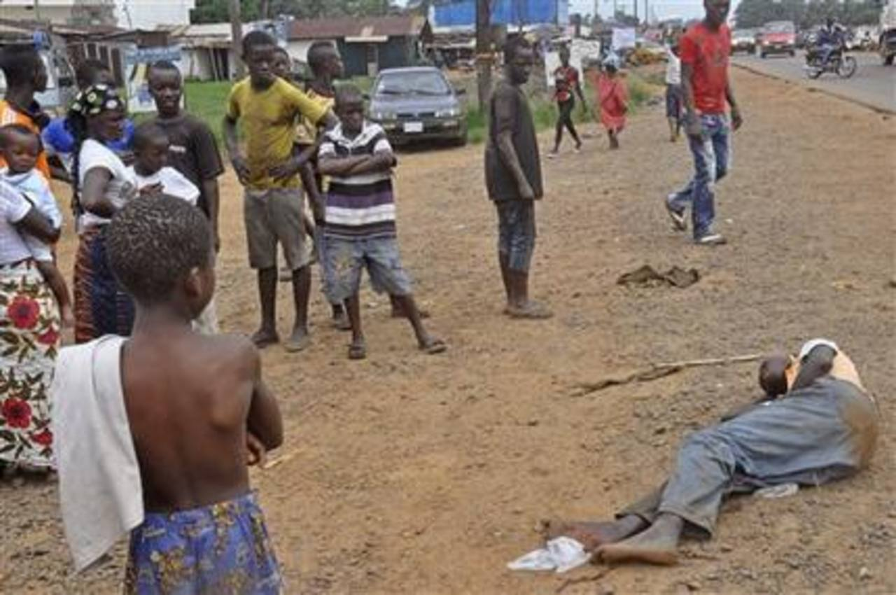 Personas rodean a un hombre que al parecer sufre de ébola en una concurrida calle de Monrovia, Liberia.