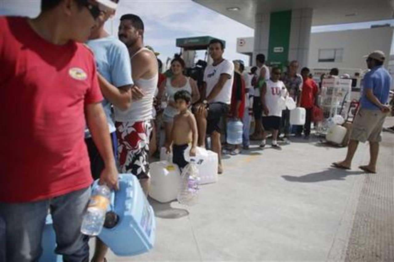 Varias personas esperando para comprar combustible en una gasolinera de Cabo San Lucas.