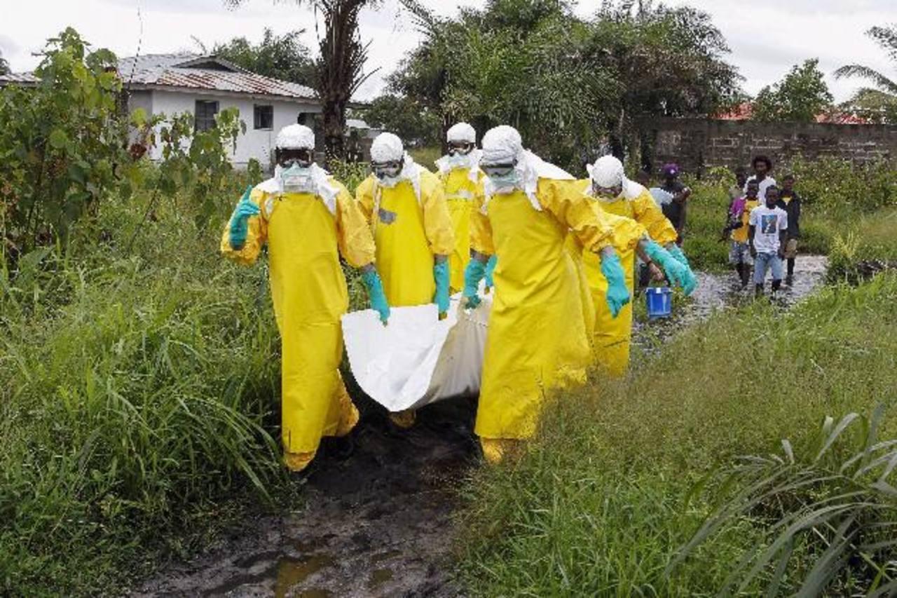 Enfermeros trasladan el cuerpo de una supuesta víctima del virus ébola en un área a las afueras de Monrovia. foto edh