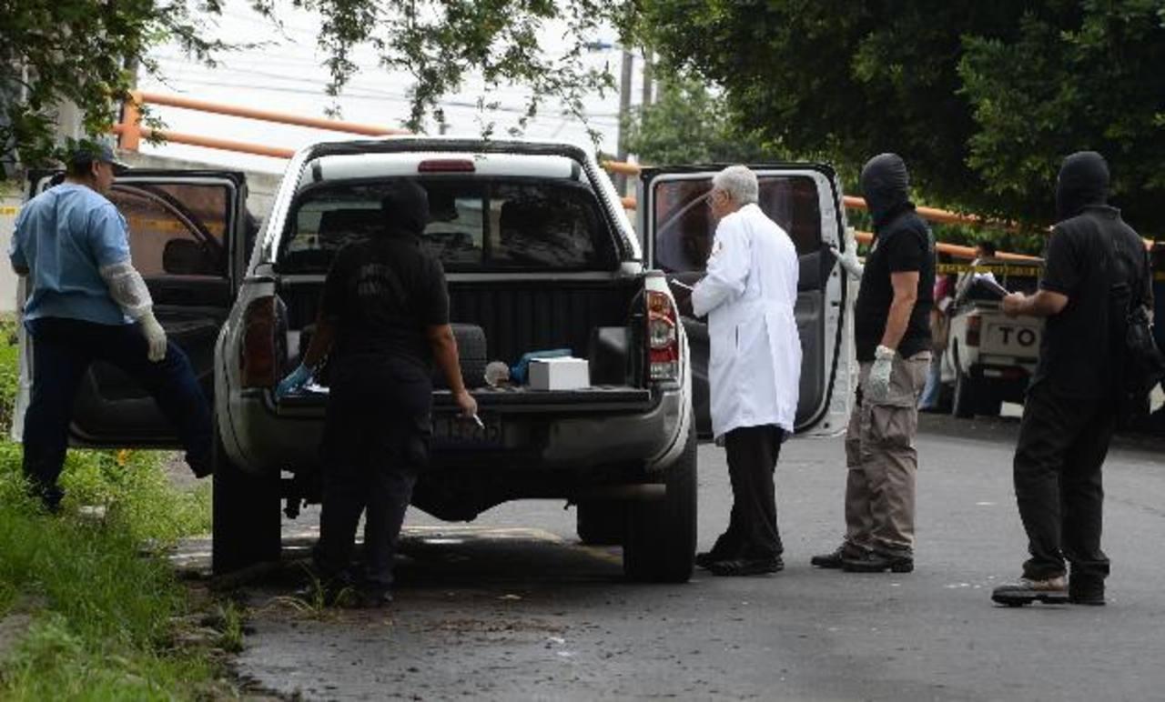 Un médico forense y un policía inspeccionan el auto en el que fue encontrado el cadáver de Josué Gabriel Rivas Campos, un comerciante de vehículos, según la PNC. fotos EDH / Jaime Anaya.