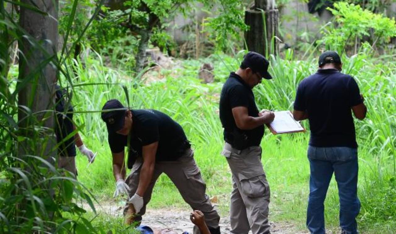 Investigadores inspeccionan el cadáver de Efraín Ezequiel Merino, asesinado ayer en Soyapango. Foto EDH /Ericka Chávez.