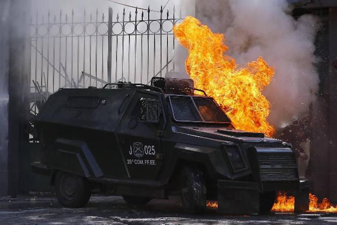 Una bomba molotov provocó que un vehículo de la policía antidisturbios se prendiera en fuego ayer durante una protesta en una escuela secundaria en Santiago. foto edh / Reuters
