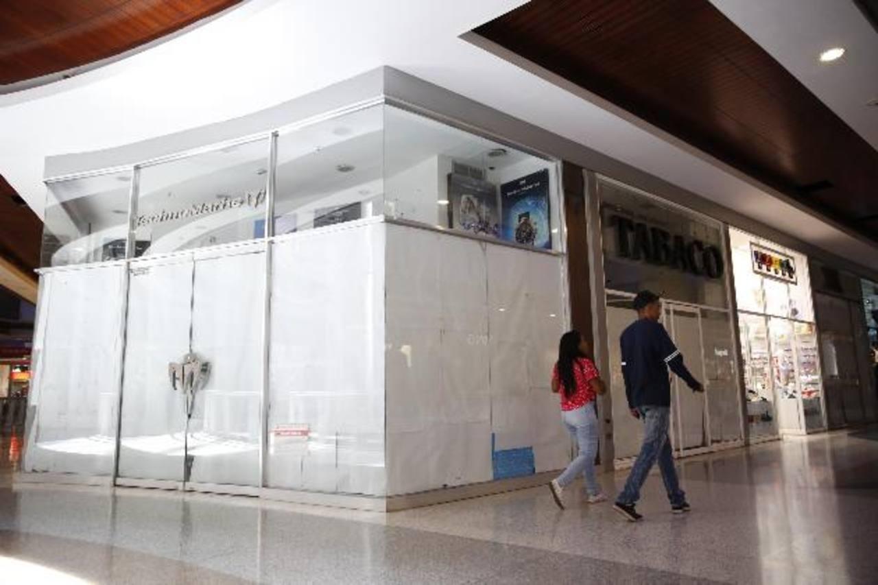 Una pareja camina dentro de un centro comercial en Caracas, donde muchos locales se ven vacíos. foto edh /Reuters