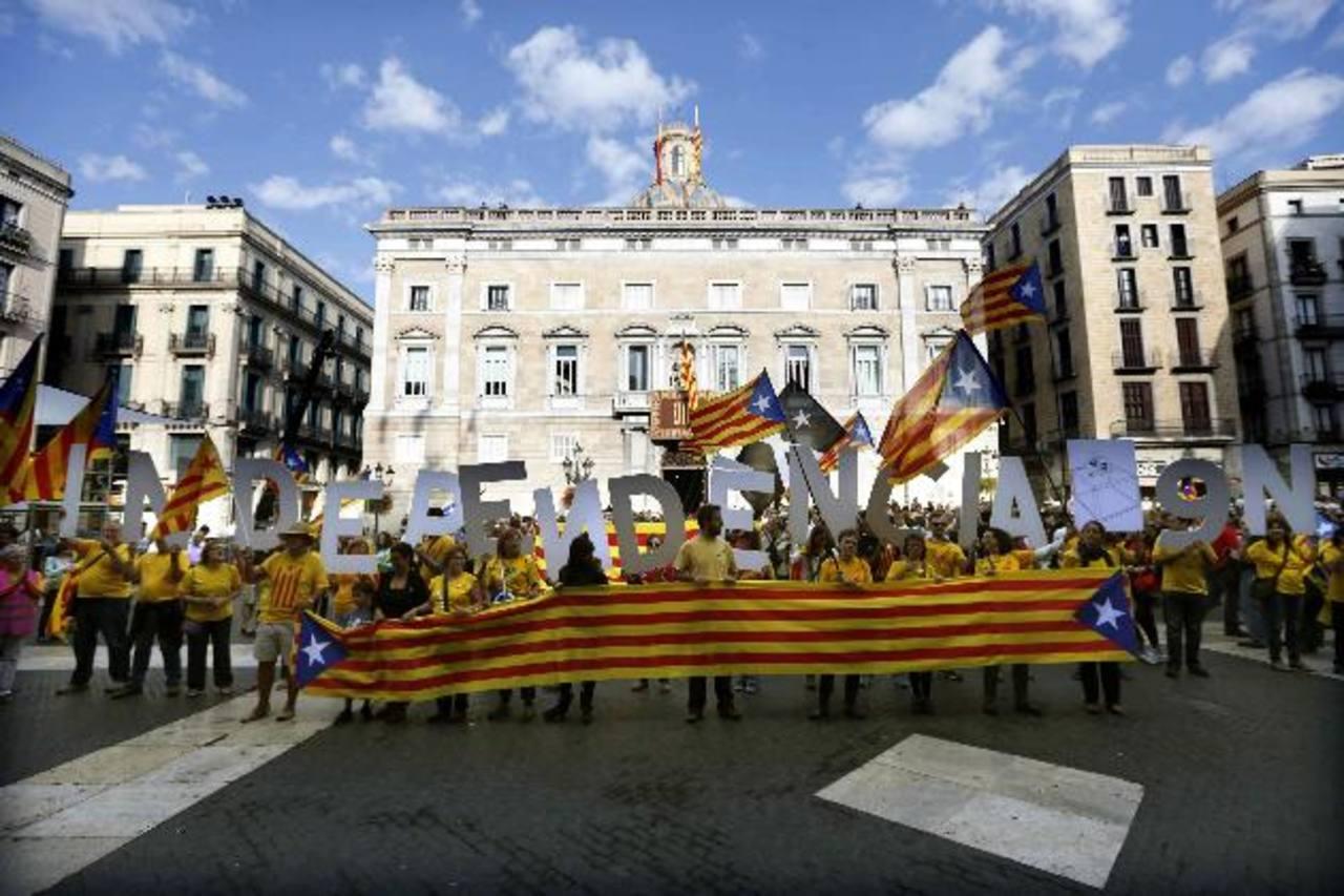 Un grupo de catalanes se concentró ayer en la plaza de Sant Jaume de Barcelona, ante el Palau de la Generalitat, donde fue firmada la convocatoria al referéndum. Foto EDH / EFE
