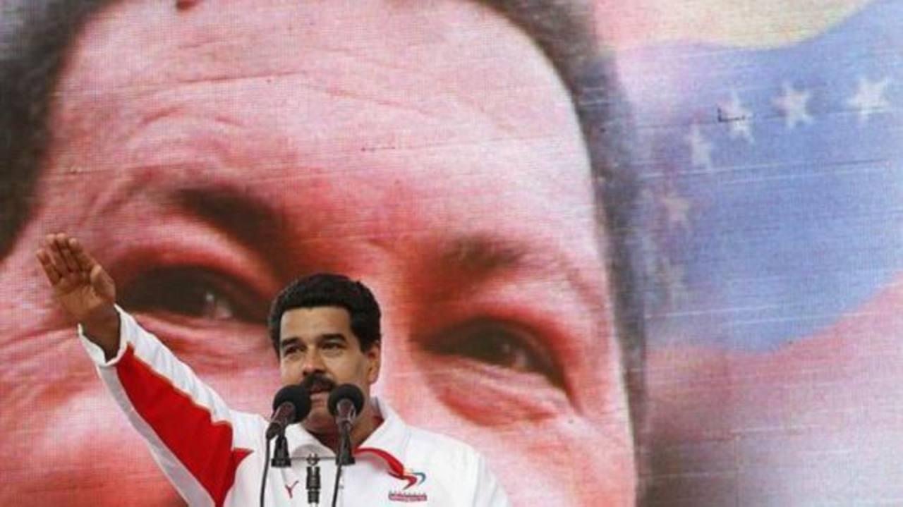 El gobernante, Nicolás Maduro, respaldado por una enorme imagen de Hugo Chávez. foto edh / reuters.