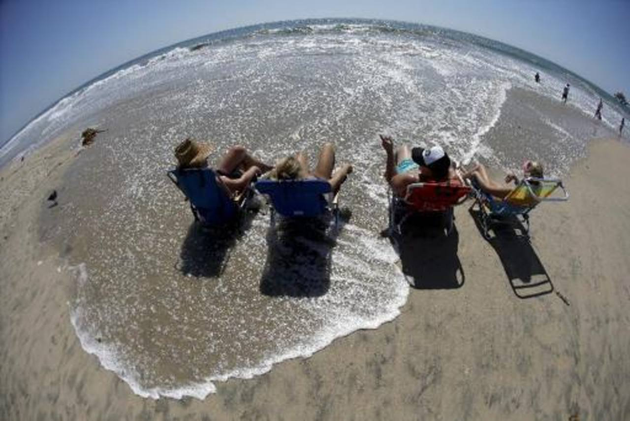 Unas personas disfrutan de la playa en California.