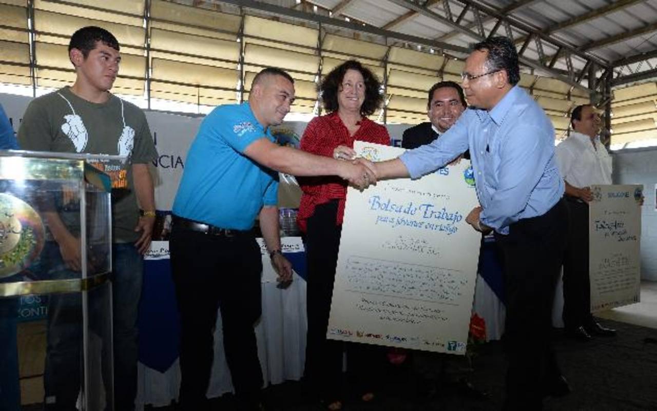"""Beth Hogan, de USAID (al centro), hace entrega del cheque al representante de Fundamicro, quien implementará la """"Bolsa de trabajo para jóvenes en riesgo"""". foto edh / marlon hernández"""