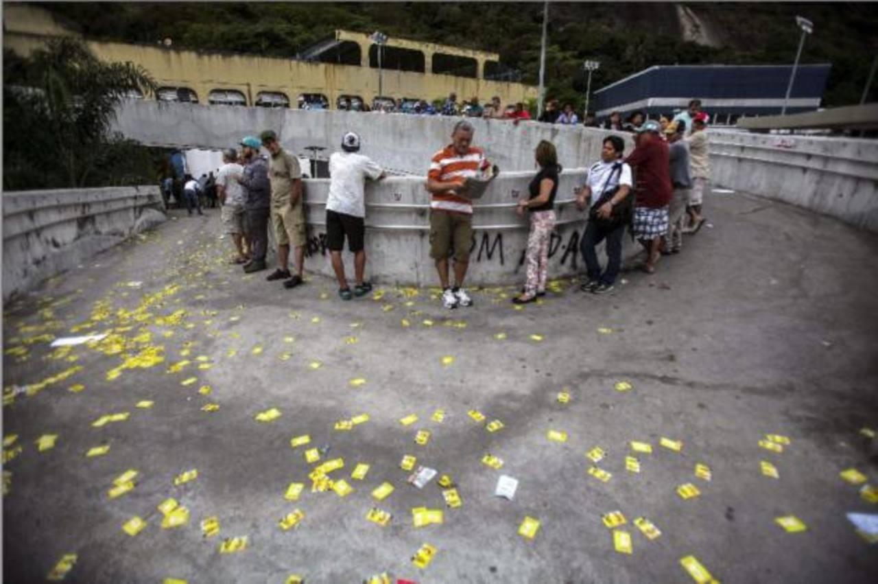Electores hacen cola para participar en la votación enfrente de la favela de Rocinha, en Río de Janeiro.