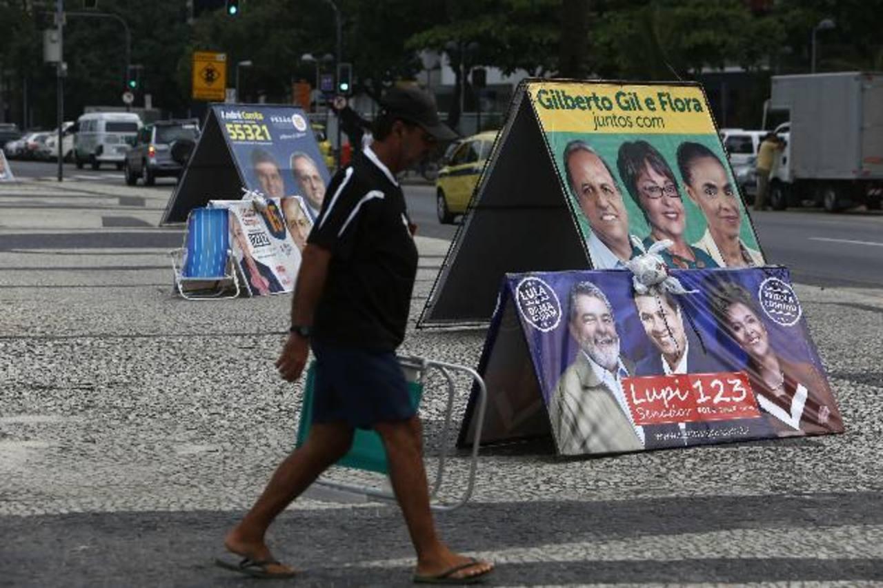 Un hombre camina frente a carteles políticos en el barrio de Copacabana ayer, en Río de Janeiro, Brasil. foto edh / efe