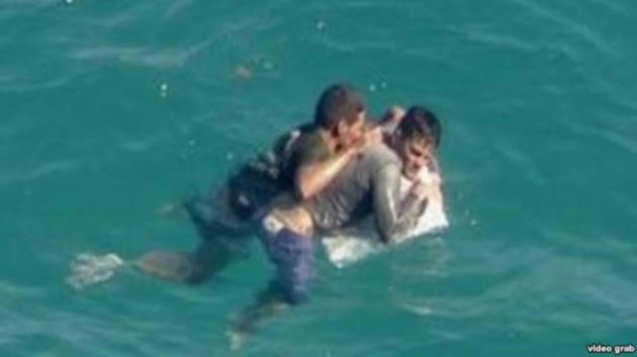 Aferrados a un pedazo de su balsa, dos cubanos esperan ser rescatados cerca de Turkey Point, al sur de Miami.