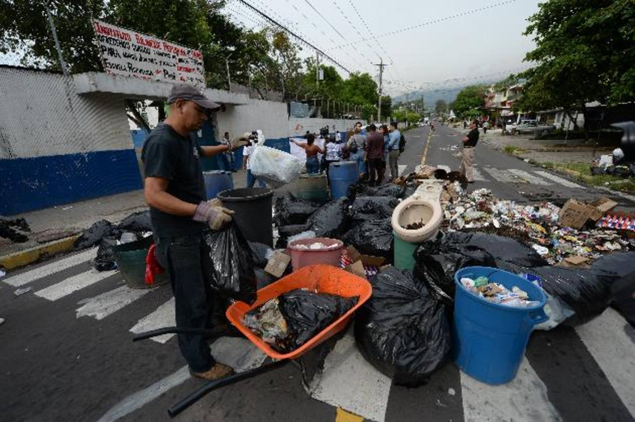 Docentes, estudiantes y padres de familia bloquearon la calle con la basura que acumularon en 22 días. Foto edh / Jaime Anaya