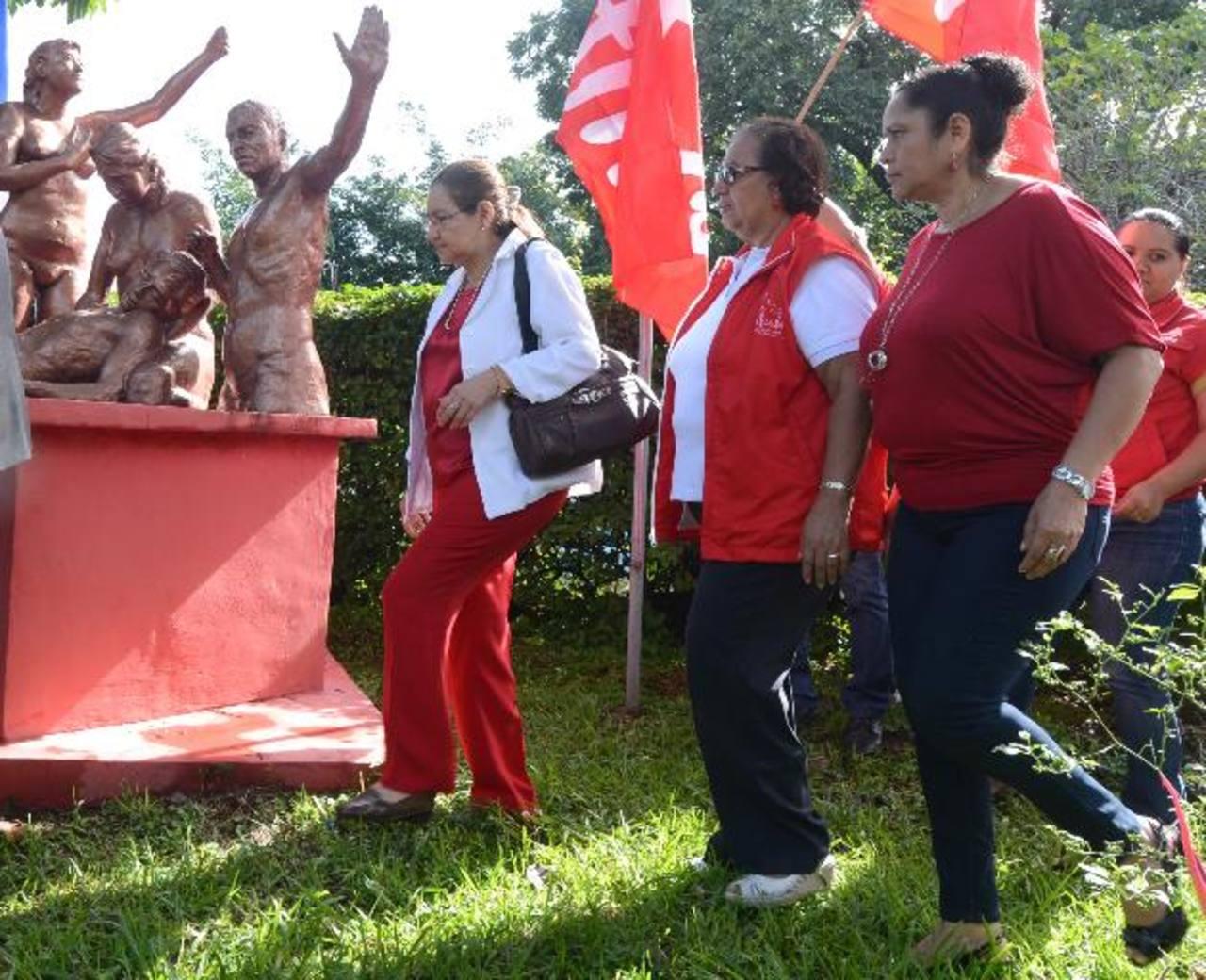 Norma Guevara, del FMLN ( izq.) colocó flores ayer en el monumento a los muertos del FMLN en su 34o. aniversario. Foto EDH / Mauricio Cáceres
