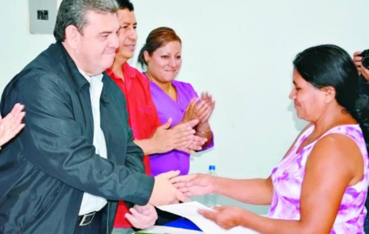 El presidente de la Cepa entrega el permiso a una de las residentes en comunidades de la línea férrea. foto edh / iris lima