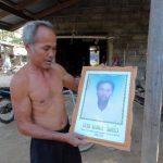 Arun Jaikaew sostiene el retrato de su hijo fallecido y que asegura ha reencarnado como el hijo de un vecino.