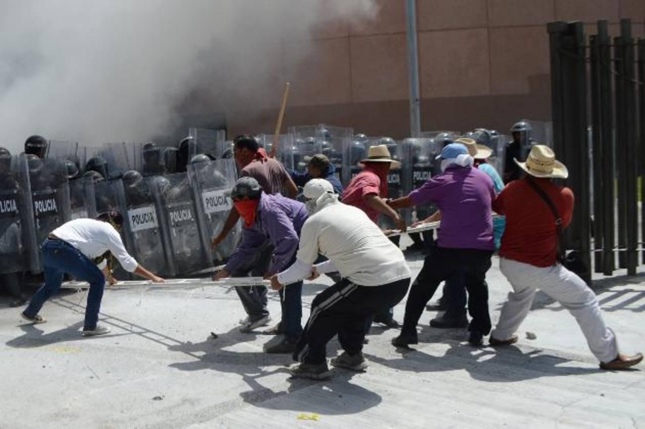 Profesores, estudiantes y familiares de los jóvenes desaparecidos se enfrentan a la policía en la sede del gobierno y del Congreso de Guerrero. Foto edh / efe