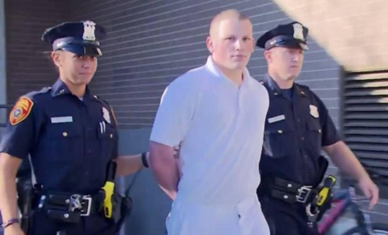 Adam Saalfield (c), de 21 años, es escoltado al Tercer Precinto de la policía. Foto EDH / newsday.com