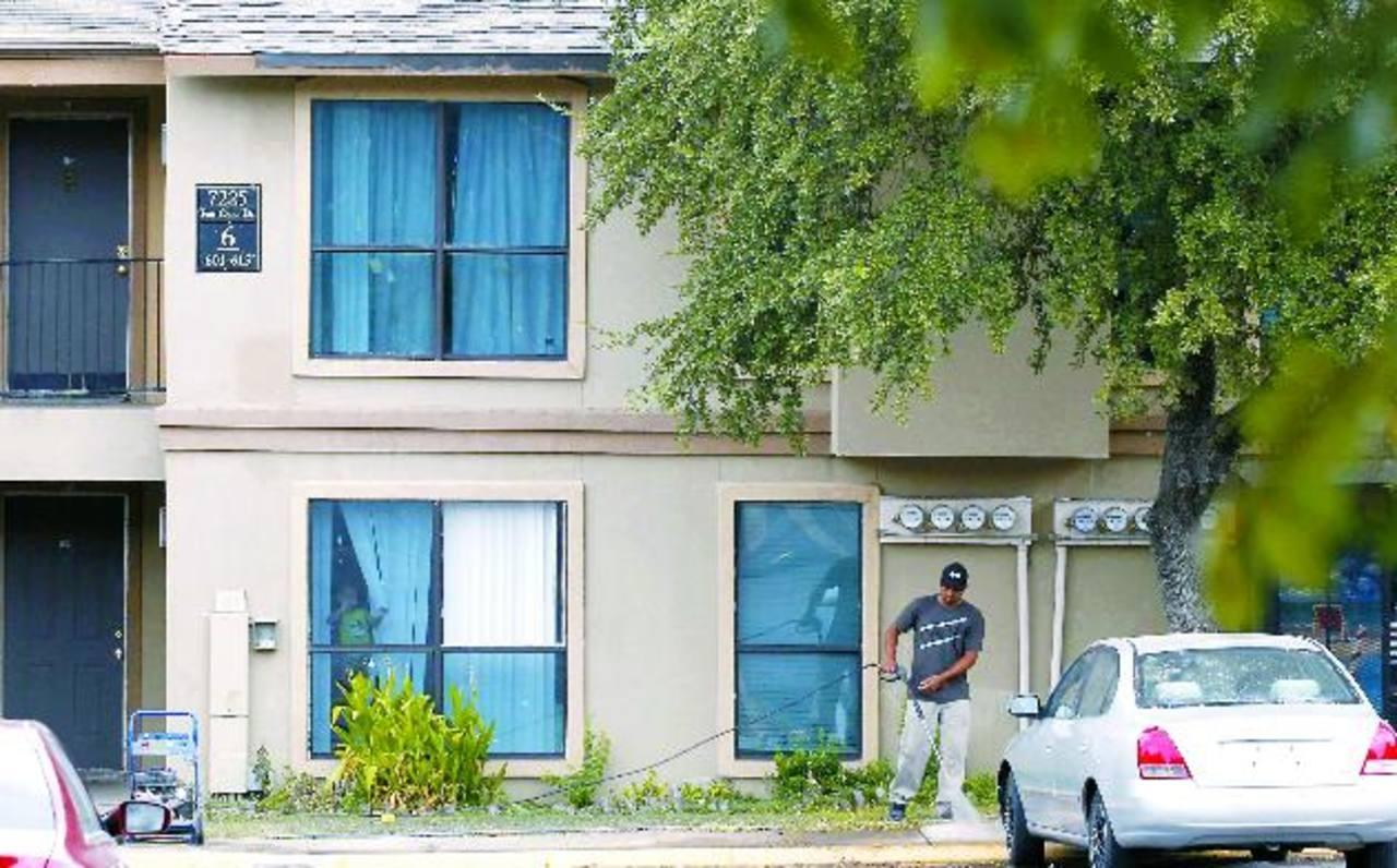 Un hombre lava la acera de los apartamentos donde vive el paciente con ébola, en Texas, EE. UU.