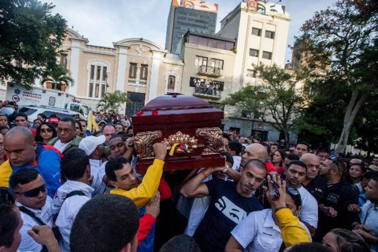 Un grupo de personas carga el féretro con los restos del diputado Robert Serra ayer, en Caracas. foto edh /EFE