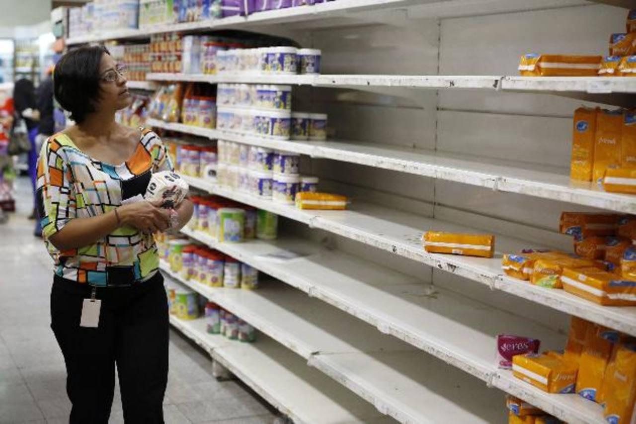 Una venezolana observa un estante con pocos productos de primera necesidad en un supermercado de Caracas, ya que la escasez en ese país se ha agudizado. Escasean los pañales desechables y los suplen con unos de tela. foto edh /archivo