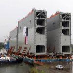 Operarios con barcos remolcadores ayudan a una barcaza gigante en el proceso de descarga del último juego de compuertas que serán instaladas en la ampliación del Canal de Panamá.