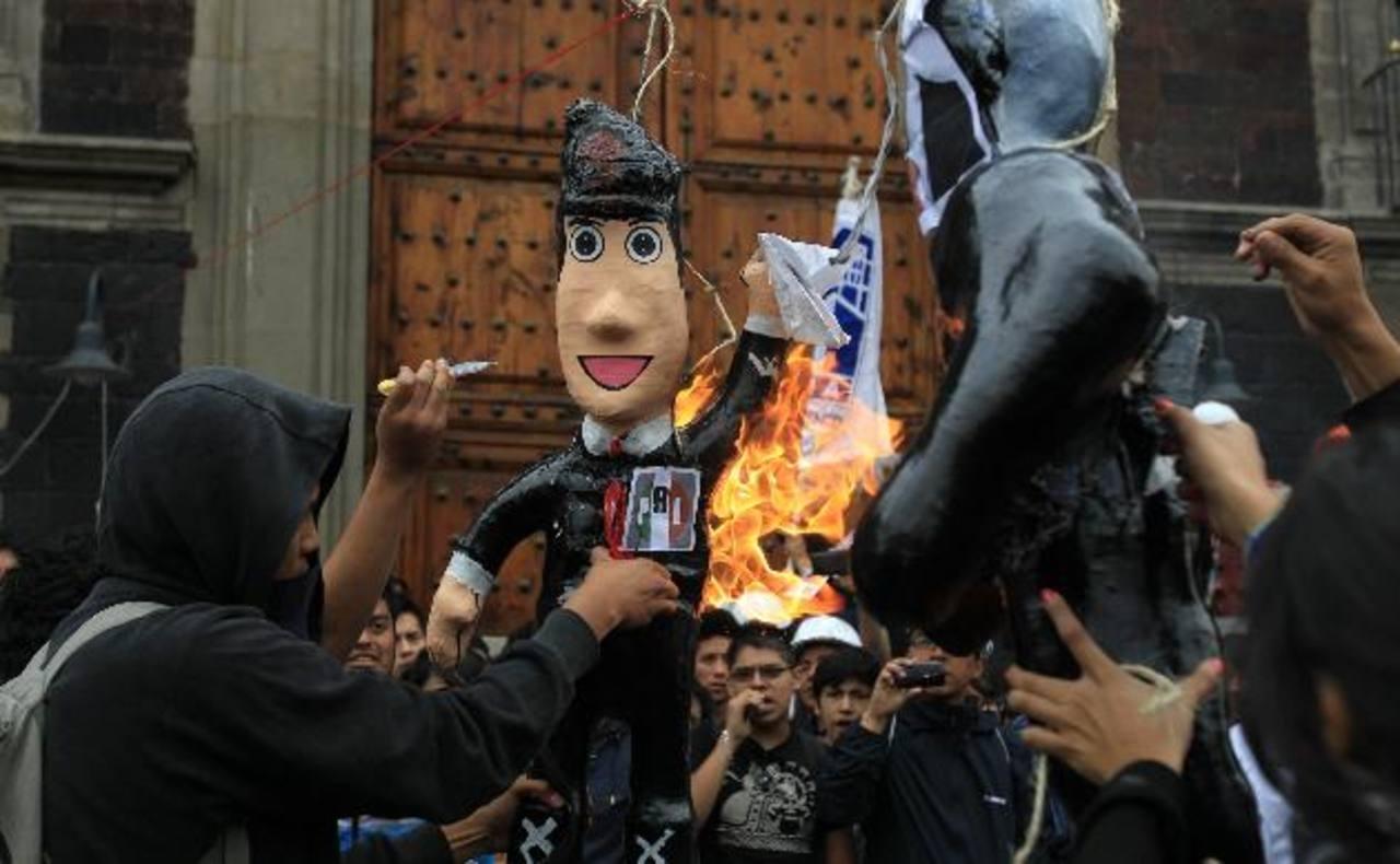 Varios estudiantes queman una escultura a las afueras del edificio de la Secretaría de Educación Pública. foto edh / efe