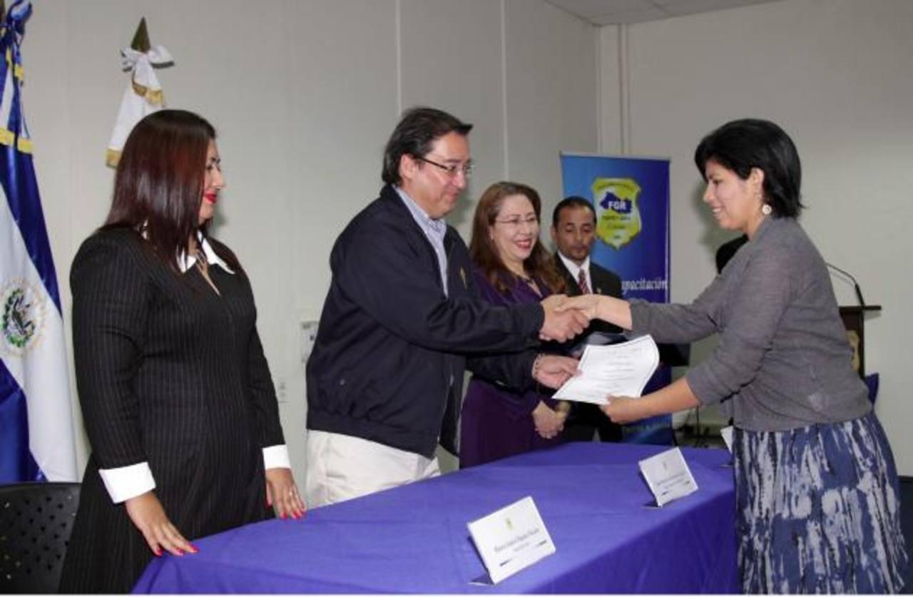Fiscal Martínez entrega escritura de propiedad a una afectada. Foto EDH