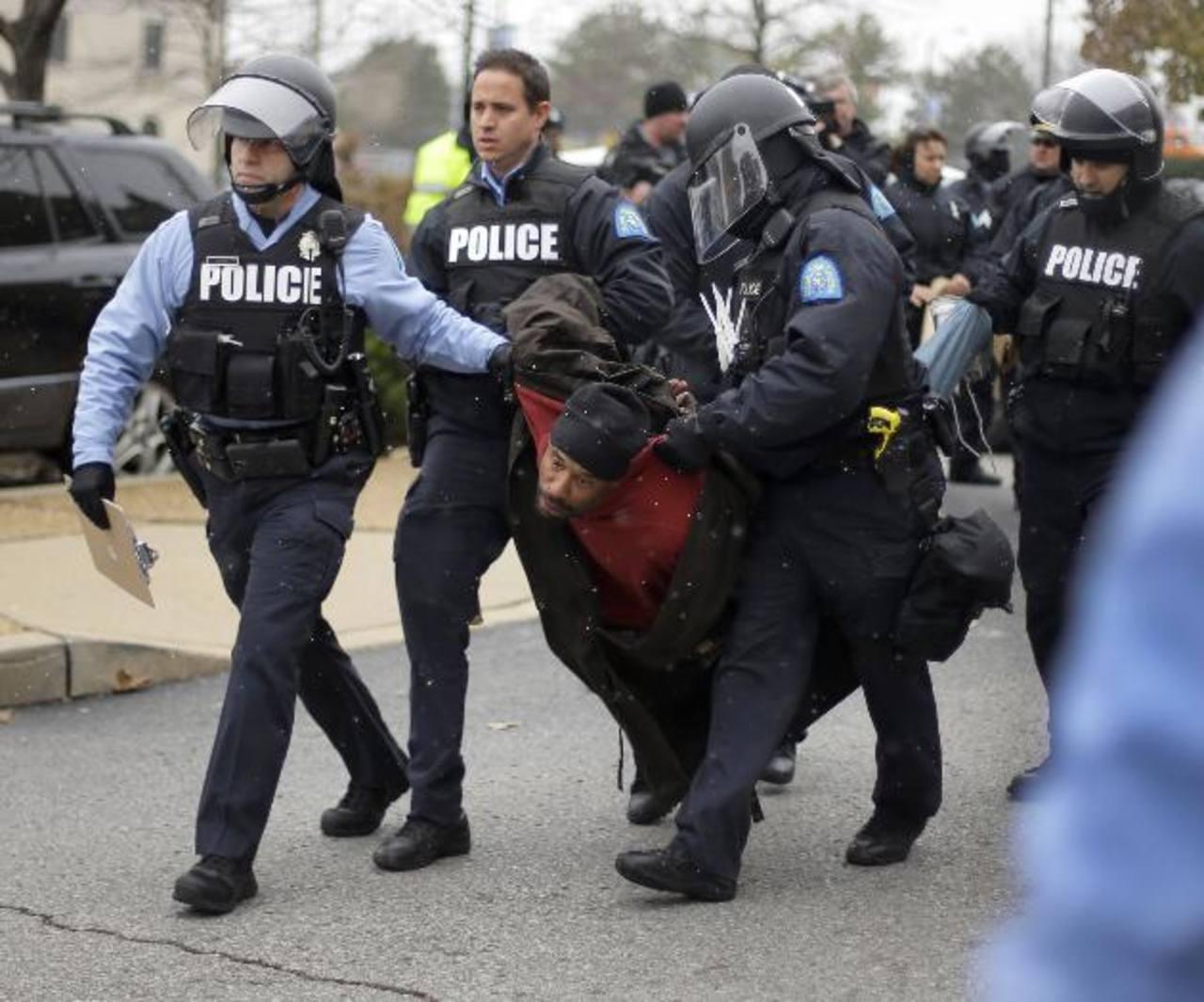 Agentes trasladan a uno de los capturados durante una protesta.