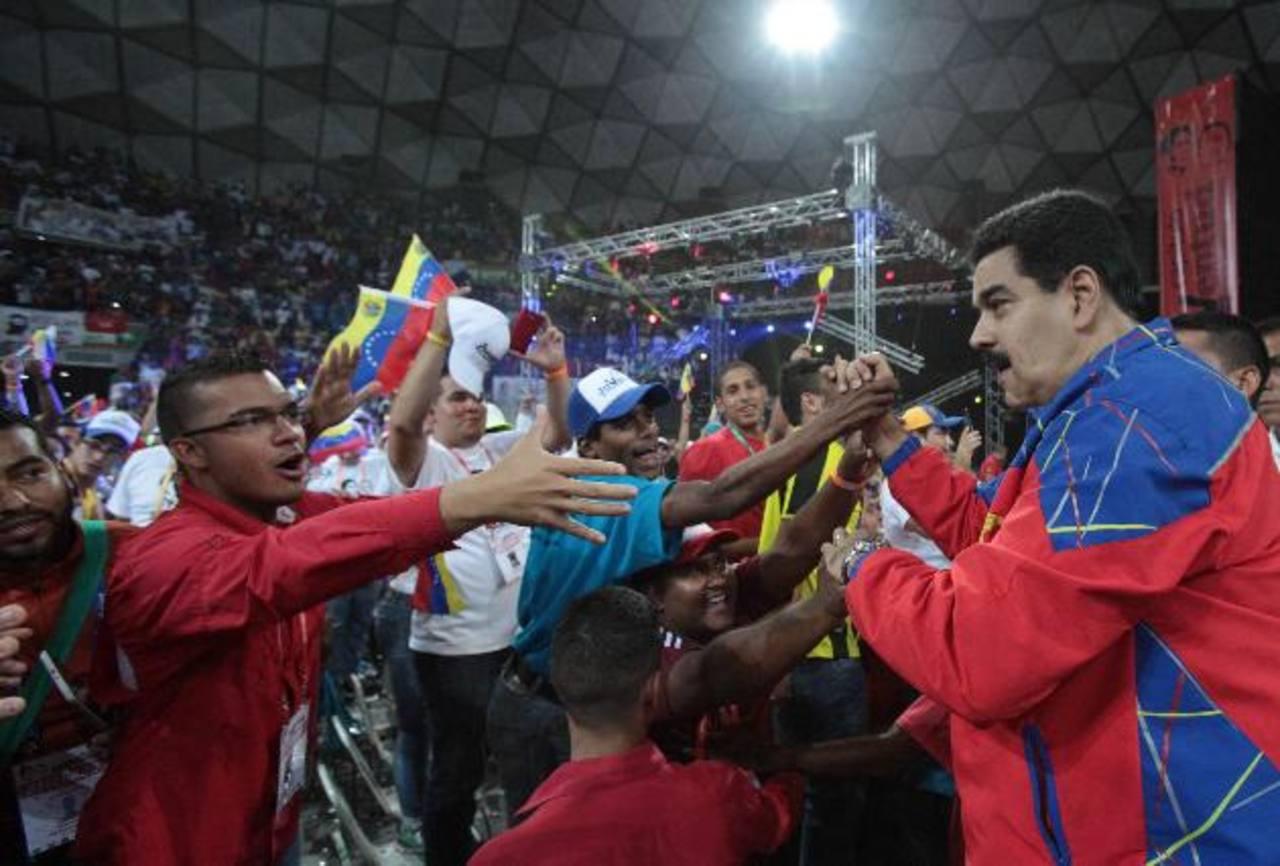 El presidente Nicolás Maduro saluda a miembros de su partido.