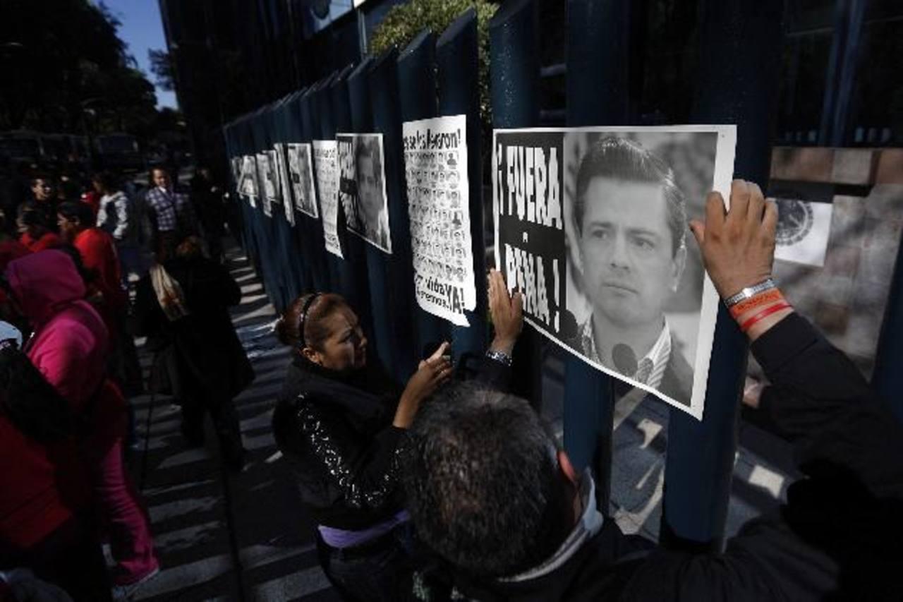 """Manifestantes cuelgan afiches con la frase: """"Fuera Peña"""", en la entrada de la oficina del procurador General de México ayer, durante una protesta en apoyo a los 43. foto edh / Reuters."""