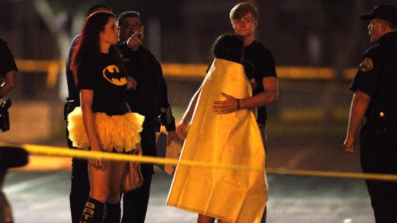 Unas 200 personas, muchos todavía disfrazados, se reunieron cerca del lugar y se consolaban unos a otros mientras veían la actividad de la policía.